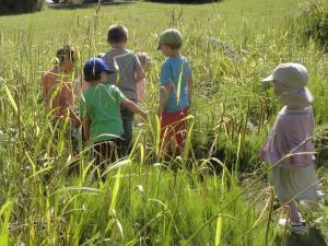 Kita-Kinder laufen über eine Wiese.